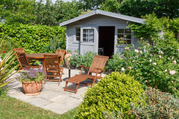 Shed with terrace and garden furniture Gray shed with terrace and wooden garden furniture shed stock pictures, royalty-free photos & images