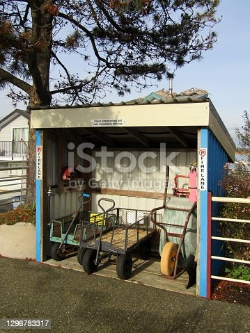 istock Shed with wheelbarrows, utility carts, hose and fire distinguisher 1296783317