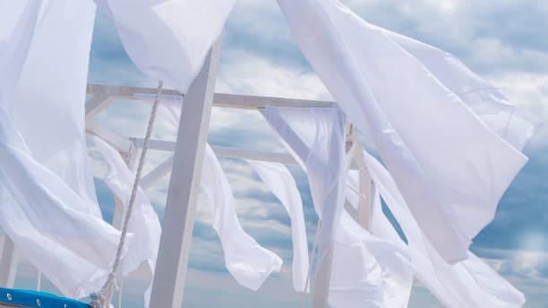 schuppen-markise mit stoff weiße vorhänge an der meeresküste brise im wind - outdoor sonnenschutz stock-fotos und bilder