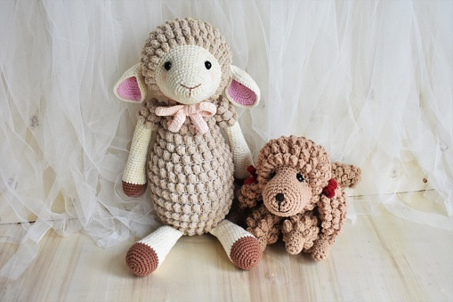 Sheep and cute poodle dog crochet, little puppy and animal toy for kids. Lamb crocheting and knitting lovely pet background with vintage theme with chiffon and wood, home decoration with soft toys on bedroom for children, teens, preschool, nursery and elementary age. Creative handmade crochet animals background