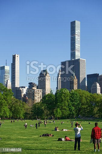 New York City, USA - 05/08/2019: The image shows Sheep Meadow in the Central Park. A lot of people are there and enjoy the beautiful weather and the sight of upper Manhattan.
