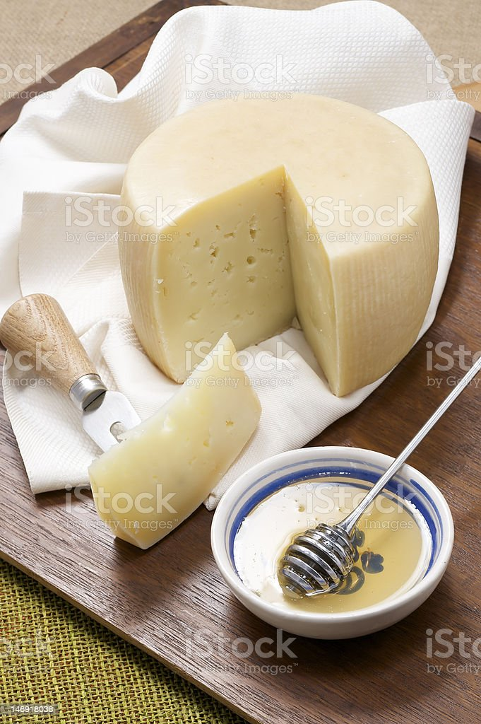 sheep milk cheese with honey on cutting board stock photo