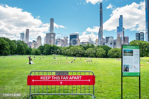 Manhattan, New york, USA - June 7, 2020: Social distancing sign placed at the entrance to Sheeps Meadow, Central Park, to enforce covid-19 pandemic guidelines to park visitors.