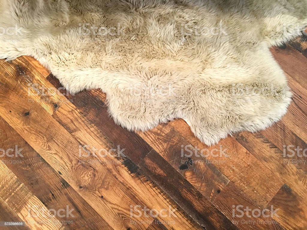Sheepskin area rug on hardwood floor stock photo