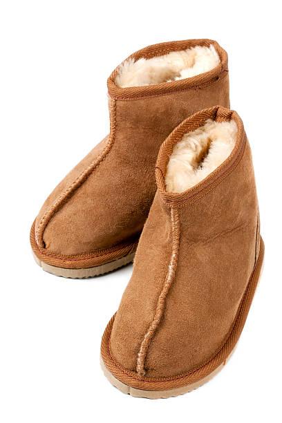 lammfell-stiefel auf weiß - lammfellstiefel stock-fotos und bilder
