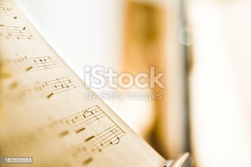 Sheet music for transverse flute on music stand. In the out of focus background a transverse flute standing vertically in its stand. Selective focus and lots of copy space.