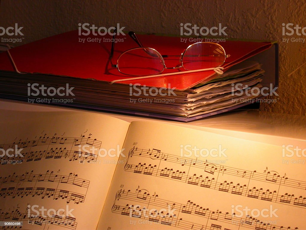 Sheet Music reading glasses on a piano in low light stock photo