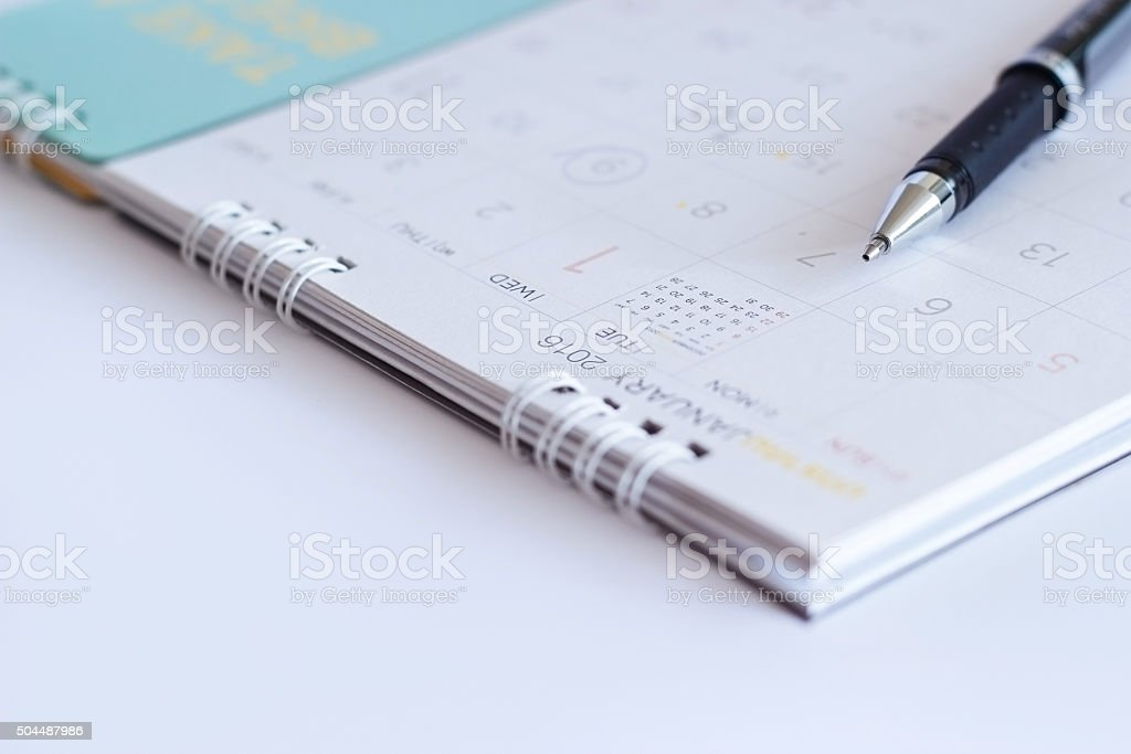 sheet of a calendar and a pen on white background stock photo