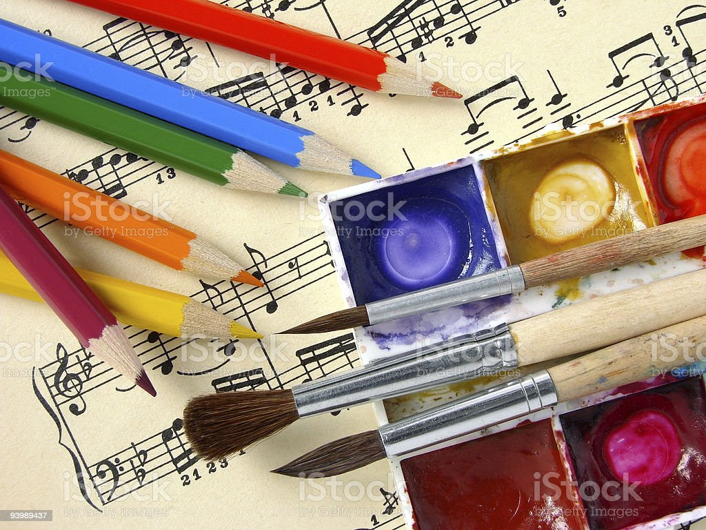 A sheet of music covered in colored pencils and paints stock photo