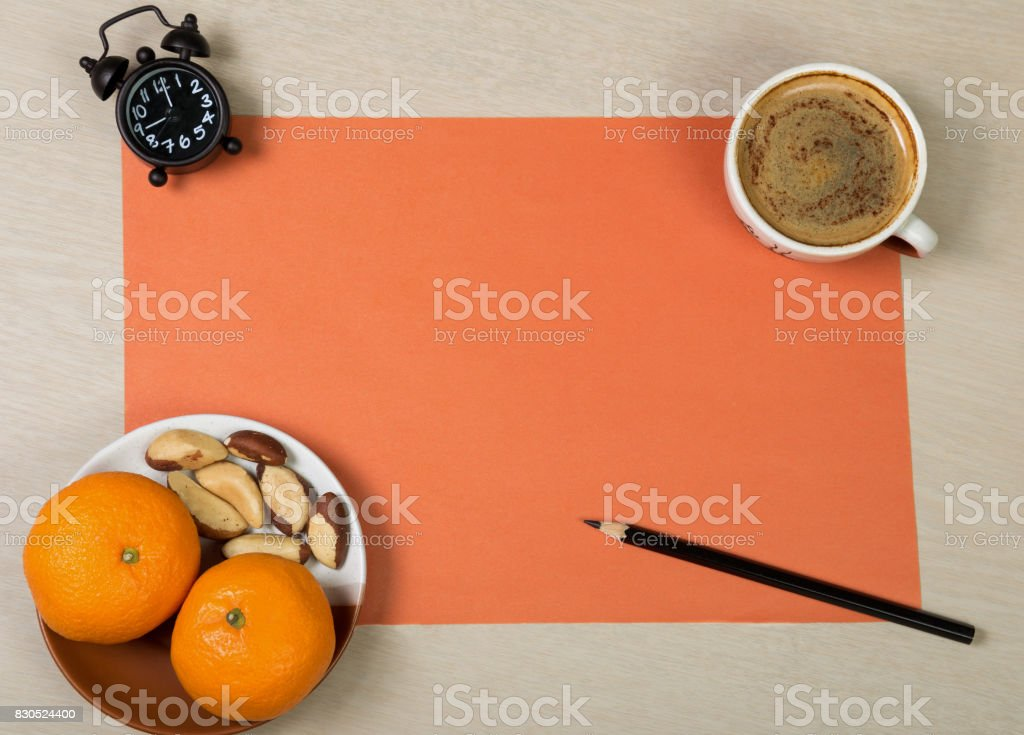 Sheet of orange paper, black pencil, clock, cup of coffee and healthy snack on light wooden background. Colorful work space. Desk dining. stock photo