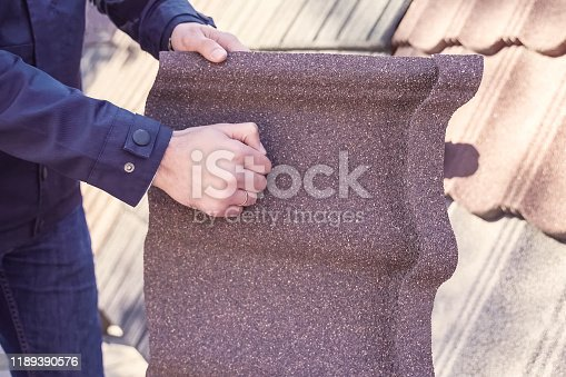 Sheet of polymer roof tiles. A worker holds a sheet of polymer plastic tile and bangs on it with his fist.