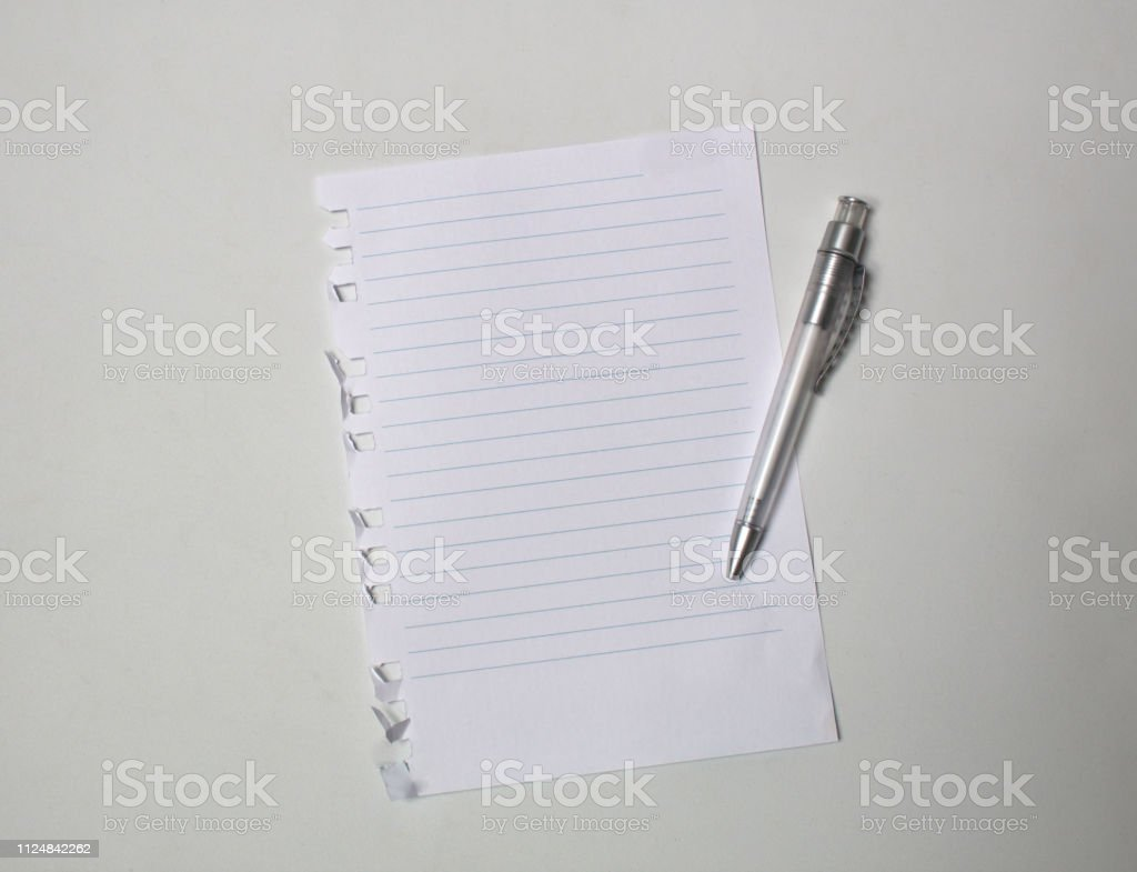 sheet of torn out notebook with pen on white background
