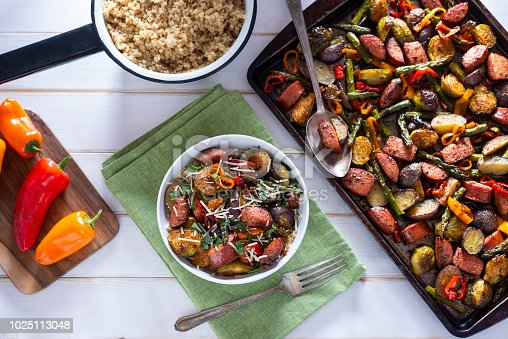 Bowl of Healthy Sheet Pan Sausage, Asparagus, Potatoes, Brussels Sprouts and Sweet Mini Peppers over Quinoa.