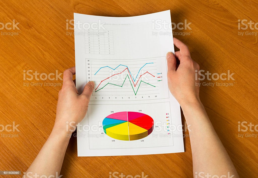 Sheet with calculations, graphs in female hands on background desktop. Lizenzfreies stock-foto