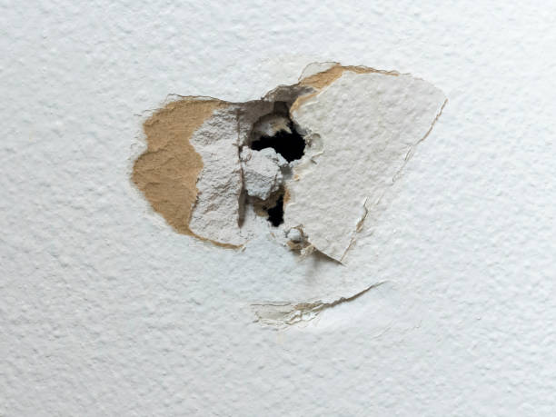 Sheetrock Home DIY Project Hole in White Drywall stock photo