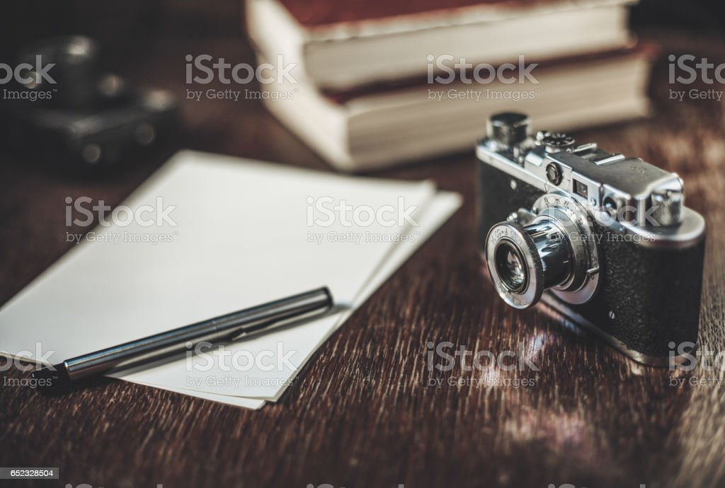 Sheets of paper, pen, retro camera and books on the table stock photo
