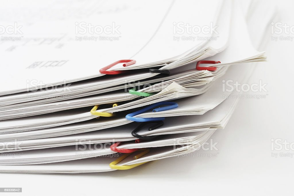 Sheets of paper pile fastened by paperclips stock photo