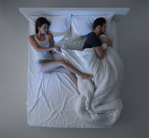 Sheets stealing Couple sleeping in bed, the man is stealing the duvet and the woman is angry and freezing duvet stock pictures, royalty-free photos & images