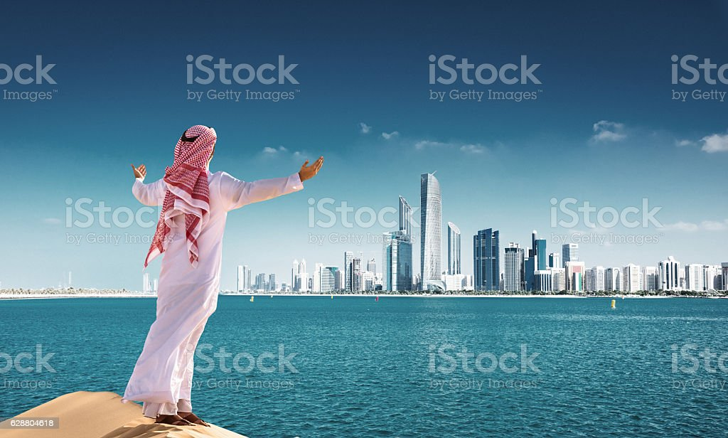 sheik prayiong against the Abu dhabi skyline waterfront​​​ foto