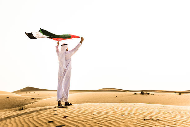 sheik waving the uae flag for national day - uae flag stok fotoğraflar ve resimler