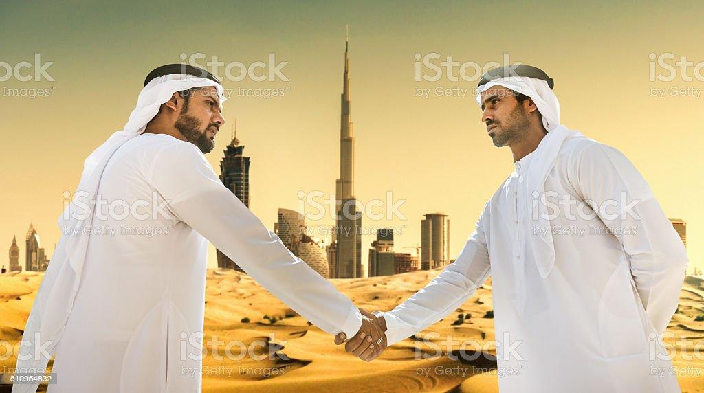 Sheik fazendo um acordo no deserto dos Emirados Árabes Unidos foto  royalty-free 5a8786c77c7e0