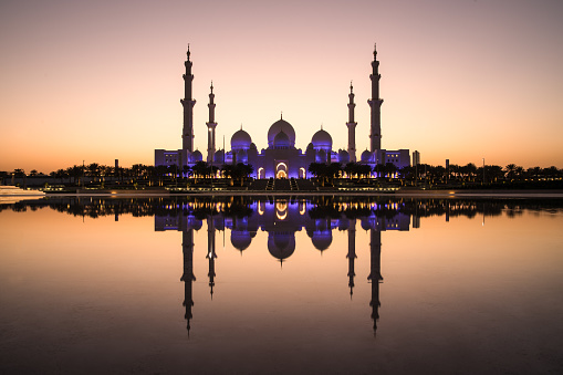 Sheikh Zayed Grand Mosque and it's perfect reflection in a water pool during dusk after sunset. Abu Dhabi, UAE.