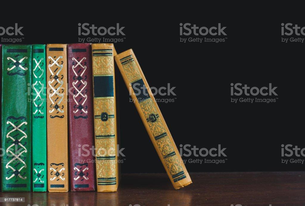 Shelf of old books on a black background stock photo