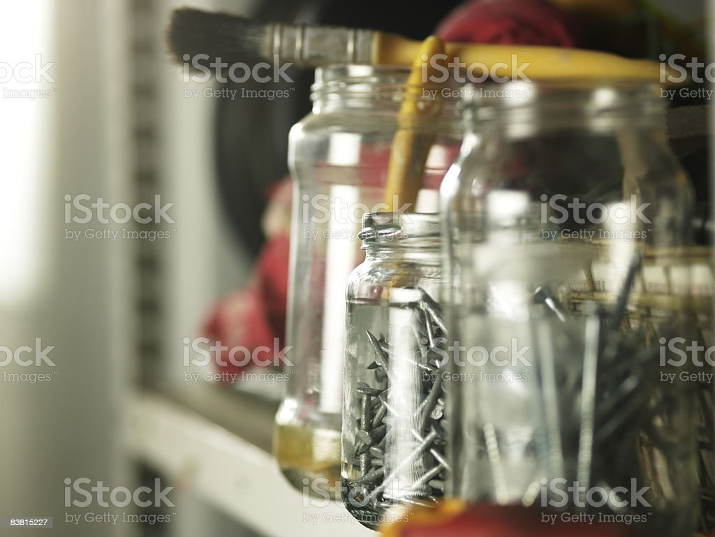 Shelf of recycled jars with nails royalty free stockfoto
