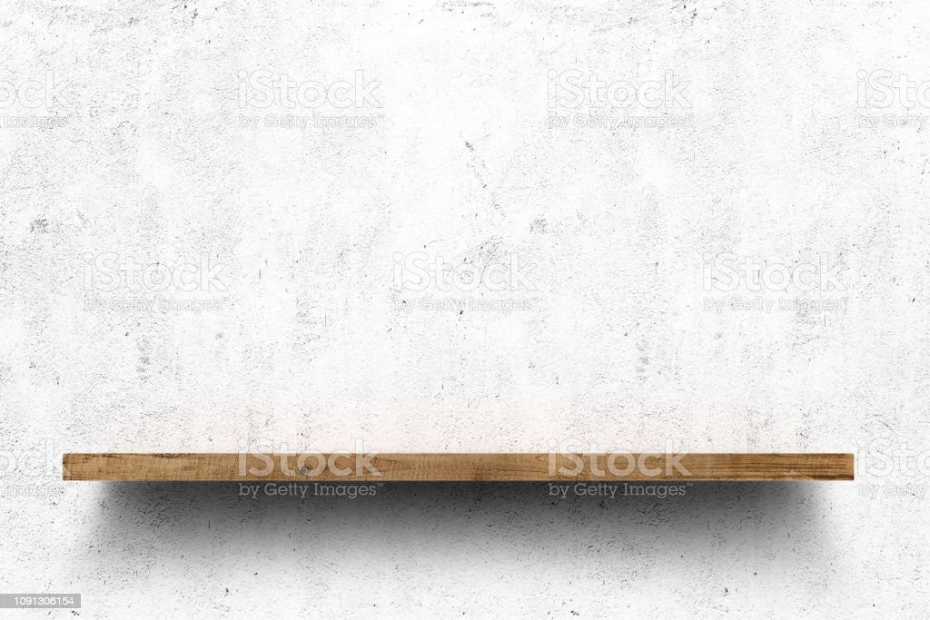 Wooden shelf over white concrete wall background