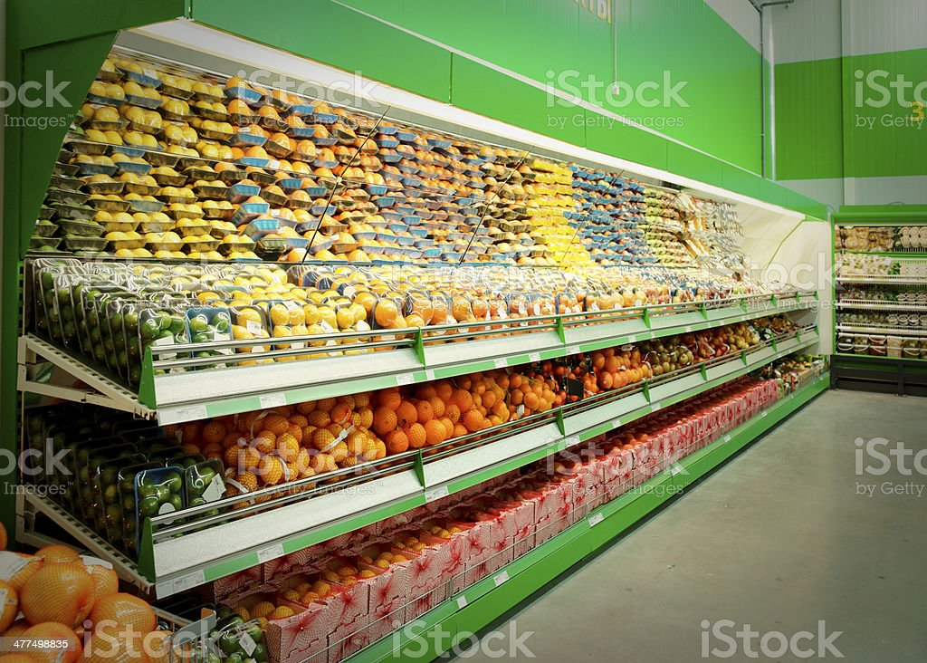 Shelf with citrus fruits in supermarket, toned royalty-free stock photo