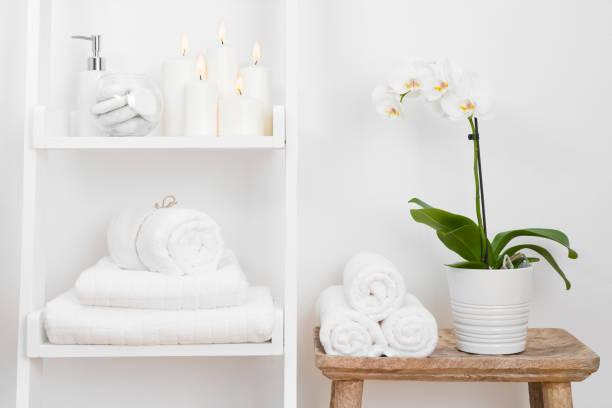 shelf with clean towels, candles, flowerpot on bathroom wooden table - prodotto per l'igiene personale foto e immagini stock