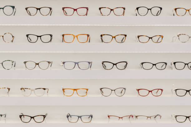 shelf with glasses in the shop,soft focus - sale lenses stock photos and pictures