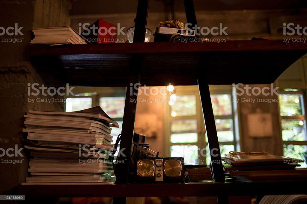 Shelf with old books, camera, clock on the vintage background stock photo