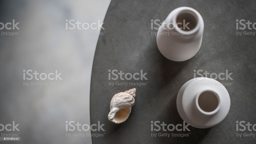 Shell and White Clay Pots on Circular Grey Scandinavian Table