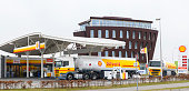 Shell fuel delivery trucks supplying a gas station with fuel in Kampen, The Netherlands. A man is fillng up his car in the background.