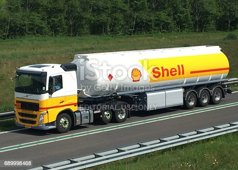 Shell fuel deliviry truck driving on the road to supply gas stations with gasoline and diesel fuel. The truck is driving on a highway near Kampen in The Netherlands during a sunny day in spring.