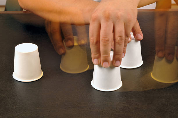 Shell Game Motion blurred image of male hands playing shell game shell game stock pictures, royalty-free photos & images