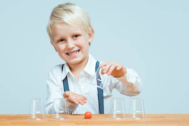 Shell game Little boy playing shell game with transparent cups shell game stock pictures, royalty-free photos & images