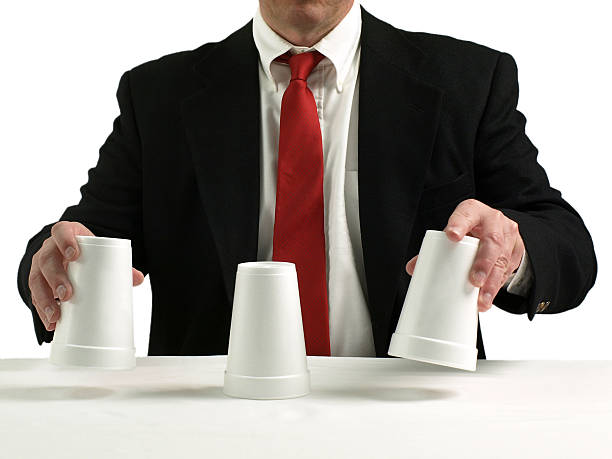 Shell game scam business man performing shell game scam with cups shell game stock pictures, royalty-free photos & images