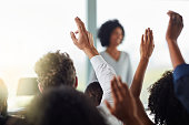 Rearview shot of a group of businesspeople with their hands raised during a seminar