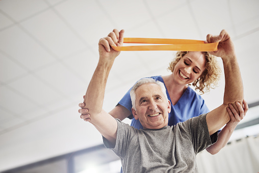 Shot of a female physician working with a senior patient in a nursing home