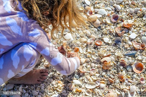 Little girl bends over a shell strewn beach, looking for treasure. The beach is covered in shells it is a beautiful, perfect, idyllic day in a tropical paradise.