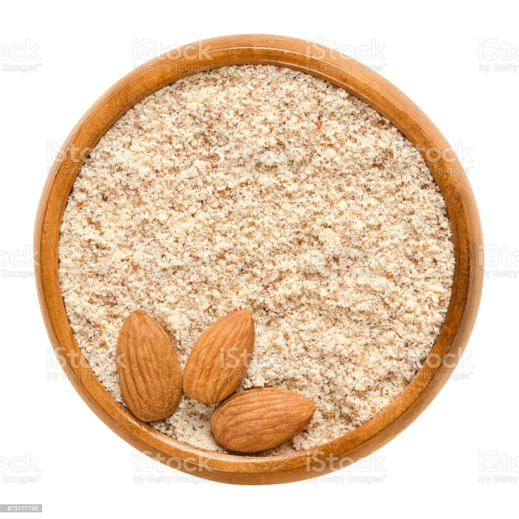Shelled and ground almond nuts in wooden bowl over white stock photo