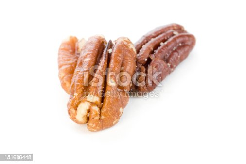 Three shelled pecans on a white background.