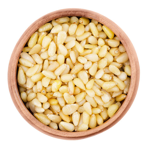 Shelled pine nuts in a bowl on white background stock photo