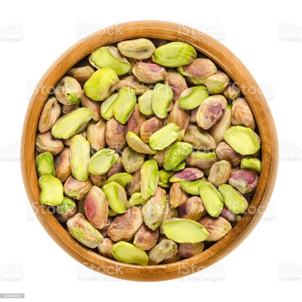 Shelled pistachio kernels in wooden bowl over white stock photo