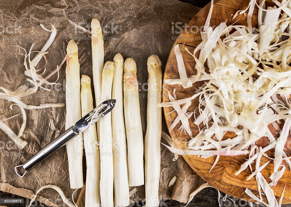 Shelled white asparagus with peelings on brown crumpled paper stock photo