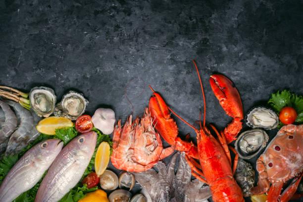 schaal-en schelpdieren en kreeftachtigen zeevruchten met selectie van verse kreeft, garnalen, vis, oesters, pijlinktvis en krab op donkere rustieke achtergrond. - krab gerecht stockfoto's en -beelden
