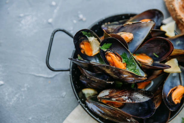 Shellfish Mussels with lemon and herbs. Shellfish seafood. Top view. Shellfish Mussels with lemon and herbs. Shellfish seafood. Top view. mussel stock pictures, royalty-free photos & images