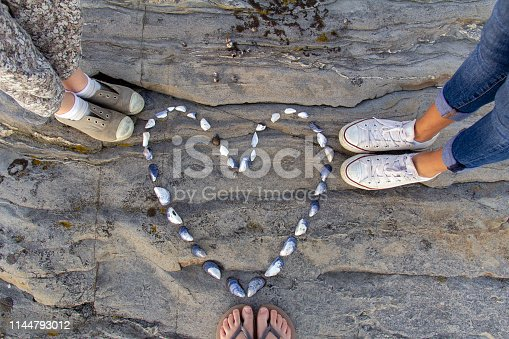 A heart made out of shells is laid out on a rock with three people standing around it. Only the feet and legs of the three persons can be seen.